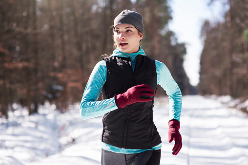 Portrait of young woman jogging in winter forest - gettyimageskorea