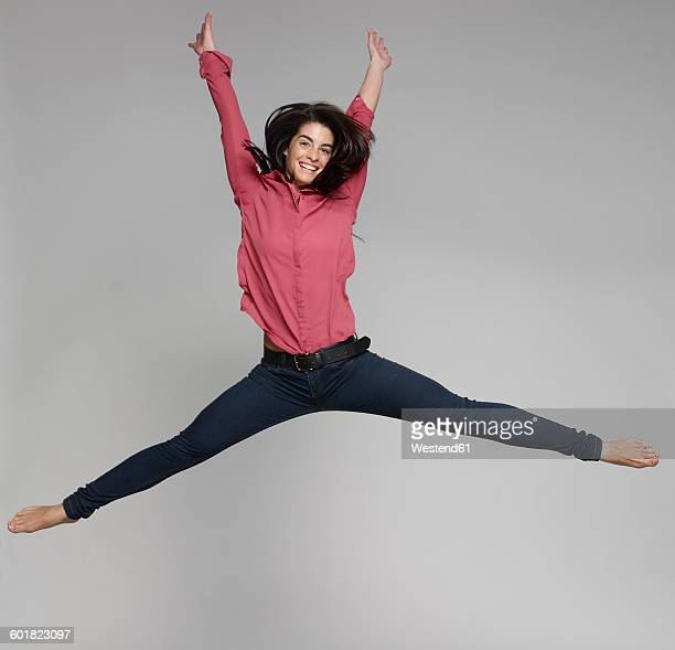 Portrait of young woman jumping in the air in front of grey background