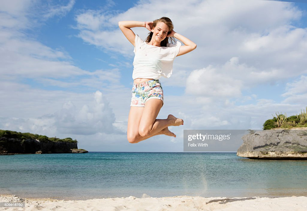 Portrait of young woman jumping on beach : Foto de stock