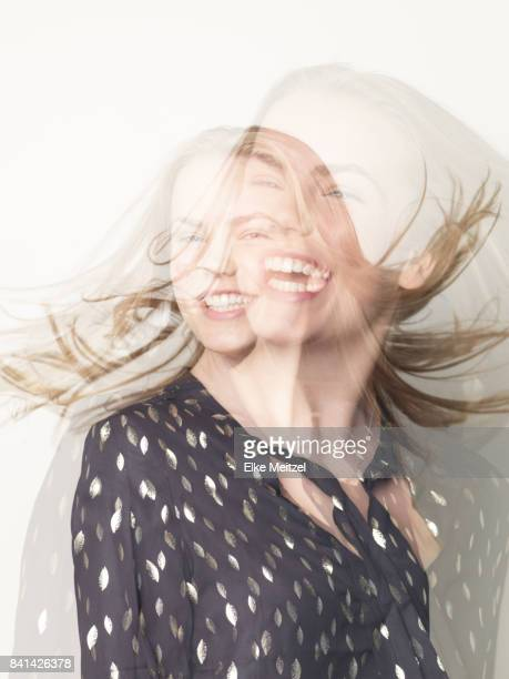 portrait of young woman laughing and moving about - mehrfachbelichtung stock-fotos und bilder