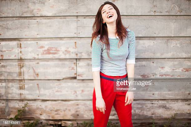 portrait of young woman laughing - red pants stock pictures, royalty-free photos & images