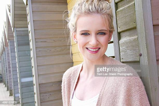 portrait of young woman leaning against beach hut - blyth northumberland stock pictures, royalty-free photos & images