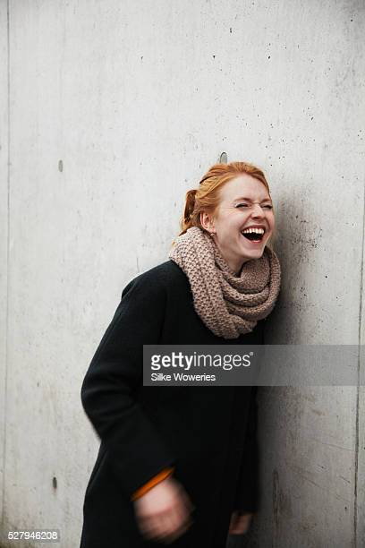 Portrait of young woman leaning against concrete wall