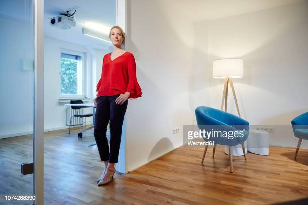 portrait of young woman leaning against doorframe in office - top garment stock pictures, royalty-free photos & images