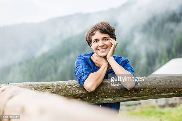 Portrait of young woman leaning against fence, Tyrol Austria