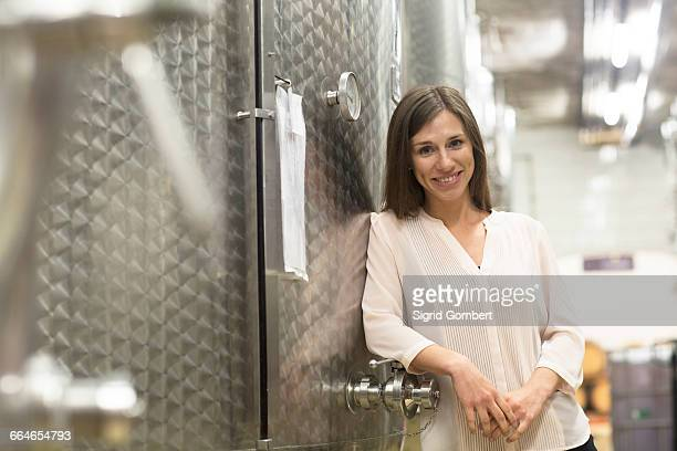 portrait of young woman, leaning against fermentation tank in wine cellar - sigrid gombert stock pictures, royalty-free photos & images