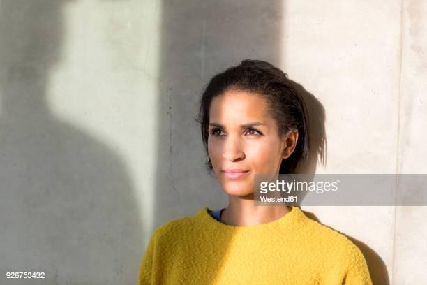 portrait of young woman leaning against wall - schlagschatten stock-fotos und bilder