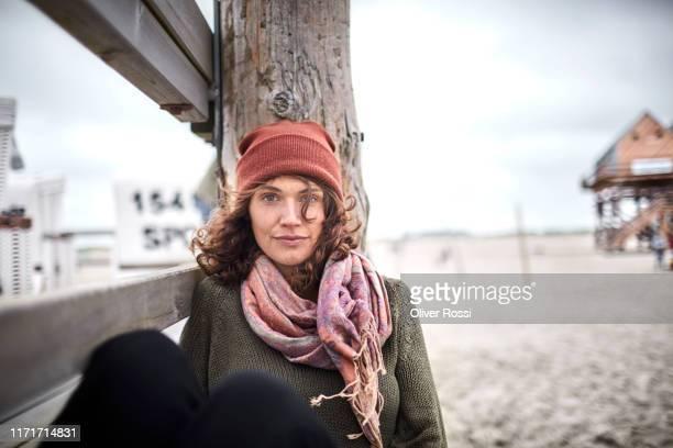 portrait of young woman leaning against wooden pole on the beach - schleswig holstein stock-fotos und bilder