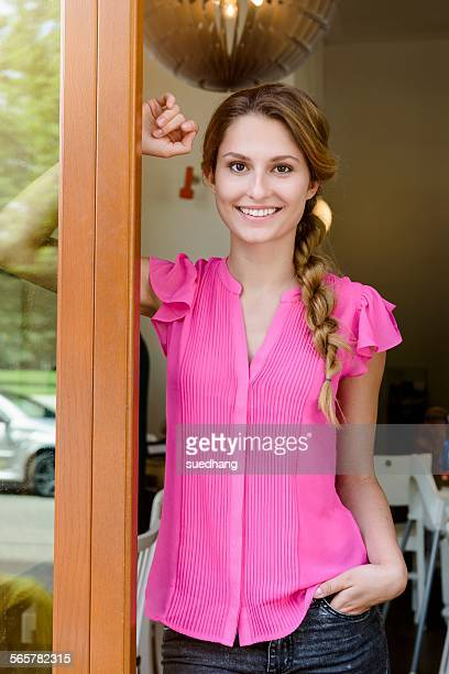 Portrait of young woman leaning on cafe doorway