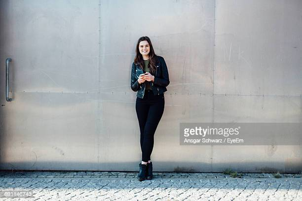 portrait of young woman leaning on metallic door - metallic jacket stock photos and pictures