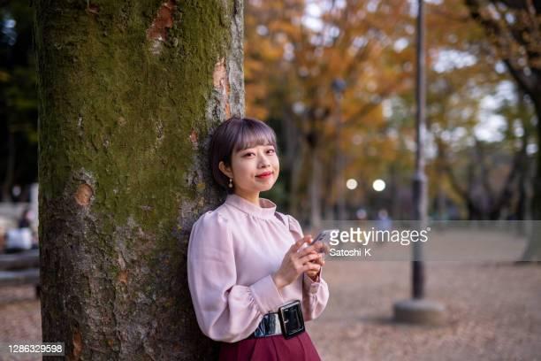 porträt einer jungen frau, die sich in der herbstsaison im öffentlichen park an einen baum lehnt - bob frisur stock-fotos und bilder