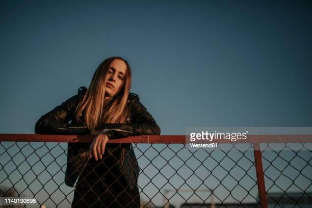 portrait of young woman leaning on wire mesh fence - chaqueta negra fotografías e imágenes de stock