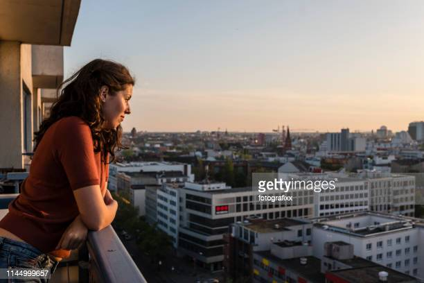 portrait of young woman leans at balcony and looks over berlin skyline while sunset - balcony stock pictures, royalty-free photos & images