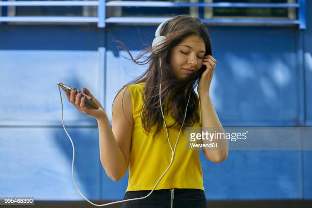 portrait of young woman listening music with headphones and cell phone - music stock-fotos und bilder