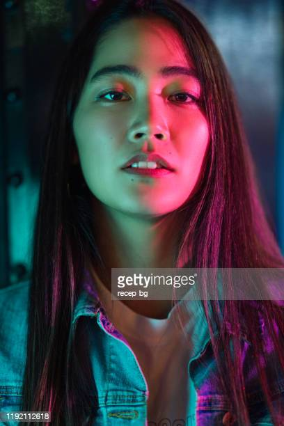 portrait of young woman lit by colorful neon lights at night - lilac fashin stock pictures, royalty-free photos & images