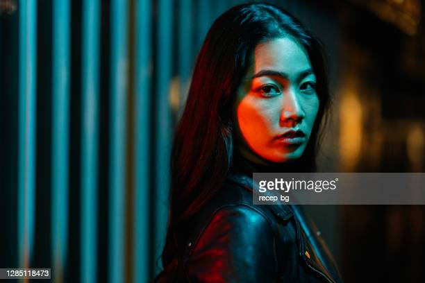portrait of young woman lit by neon colored light in city at night - fashion model stock pictures, royalty-free photos & images