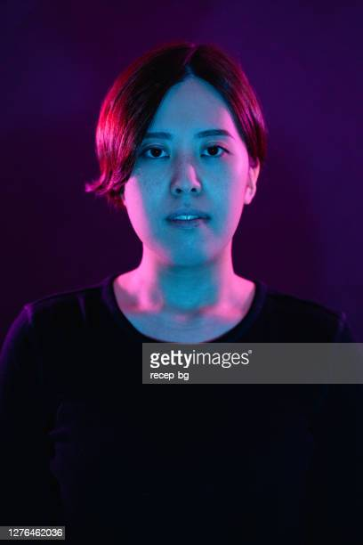 portrait of young woman lit by neon colored lights - millennial pink stock pictures, royalty-free photos & images