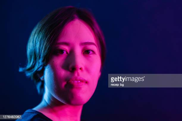 portrait of young woman lit by neon colored lights - illuminated stock pictures, royalty-free photos & images