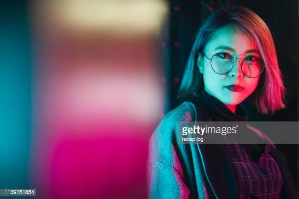 retrato de mujer joven iluminada por luces de neón - letrero de neón fotografías e imágenes de stock
