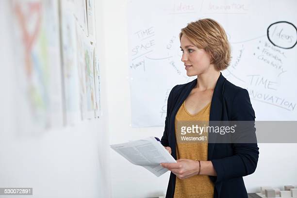 Portrait of young woman looking at a wall with concepts in an office