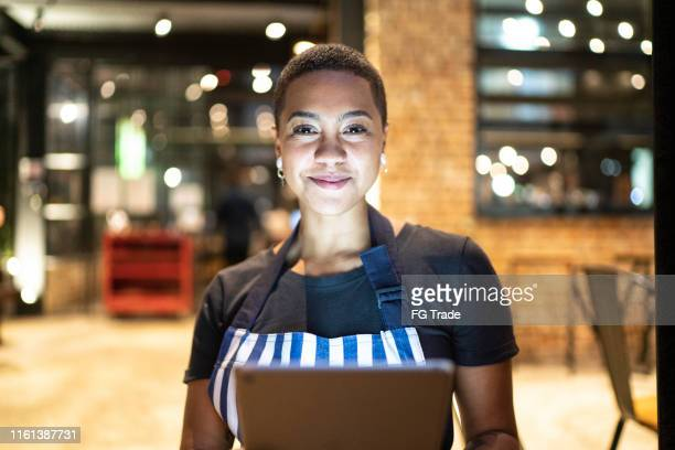 portrait of young woman looking at camera and holding a digital tablet at restaurant - pizzeria stock pictures, royalty-free photos & images