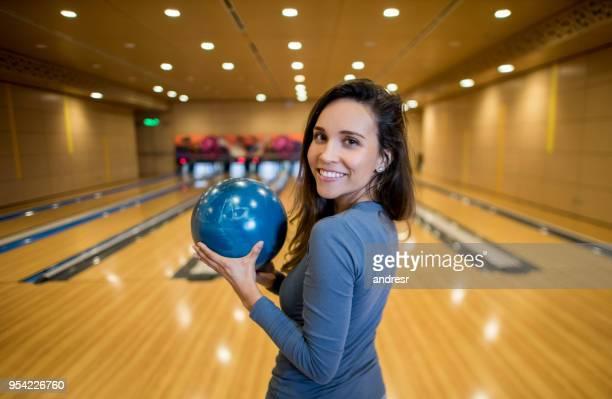 Porträt der jungen Frau, Blick in die Kamera Lächeln eine Bowlingkugel mit gedrückter