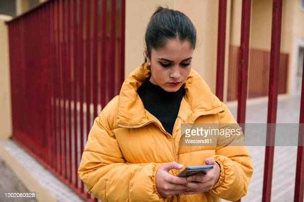 portrait of young woman looking at cell phone outdoors - padded jacket stock pictures, royalty-free photos & images