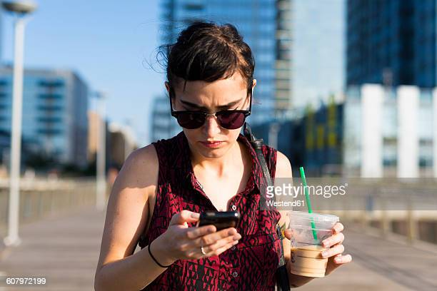 Portrait of young woman looking at her smartphone