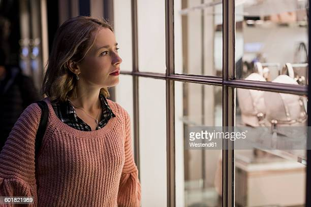Portrait of young woman looking into window display in the evening