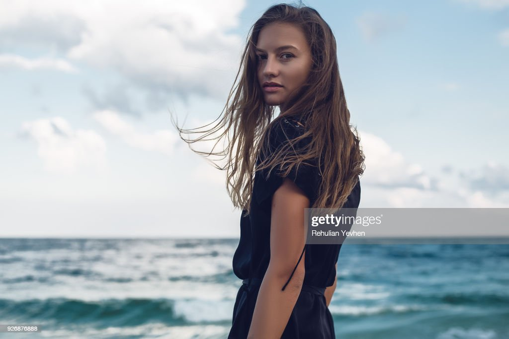 Portrait of young woman looking over her shoulder on beach, Odessa, Odessa Oblast, Ukraine : Stock Photo