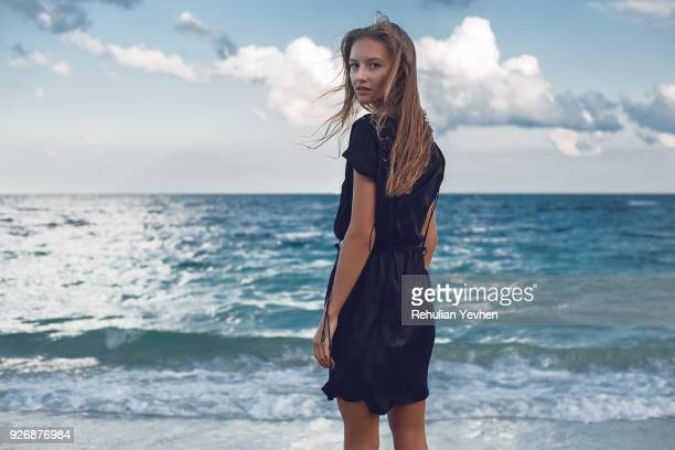 portrait of young woman looking over her shoulder on beach, odessa, odessa oblast, ukraine - one young woman only stock pictures, royalty-free photos & images