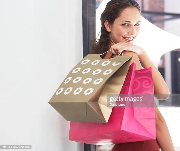 Portrait of young woman looking over shoulder, holding shopping bags