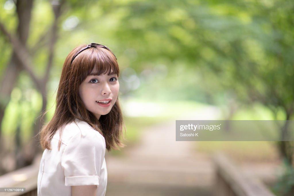 公共の公園で肩越しに見ている若い女性の肖像画 : ストックフォト