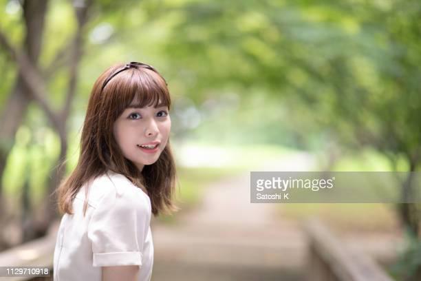 portrait de jeune femme regardant par dessus l'épaule en parc public - femme japonaise belle photos et images de collection