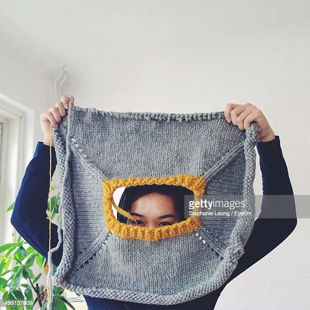 Portrait of young woman looking through knitted cloth