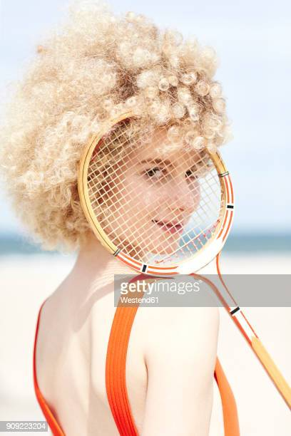 portrait of young woman looking through reticule of tennis racket on the beach - afro stock pictures, royalty-free photos & images
