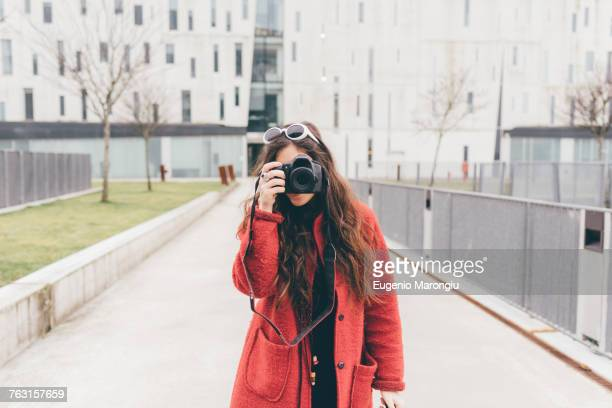 Portrait of young woman, looking through viewfinder of camera