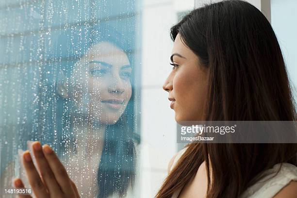 Portrait of young woman looking through window in rainy day