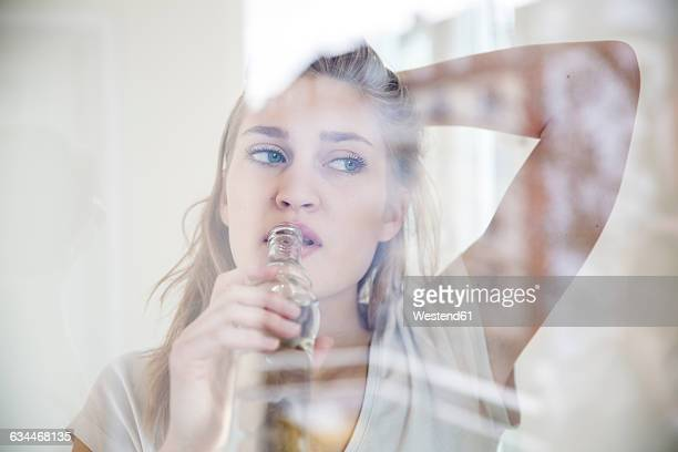 Portrait of young woman looking through windowpane while drinking water