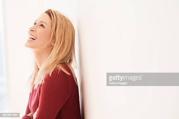 Portrait of young woman looking up and laughing
