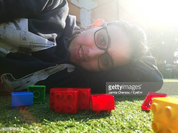 Portrait Of Young Woman Lying By Toy Blocks On Field