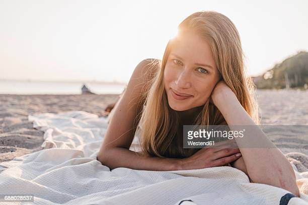 portrait of young woman lying on blanket on the beach - off shoulder stock pictures, royalty-free photos & images