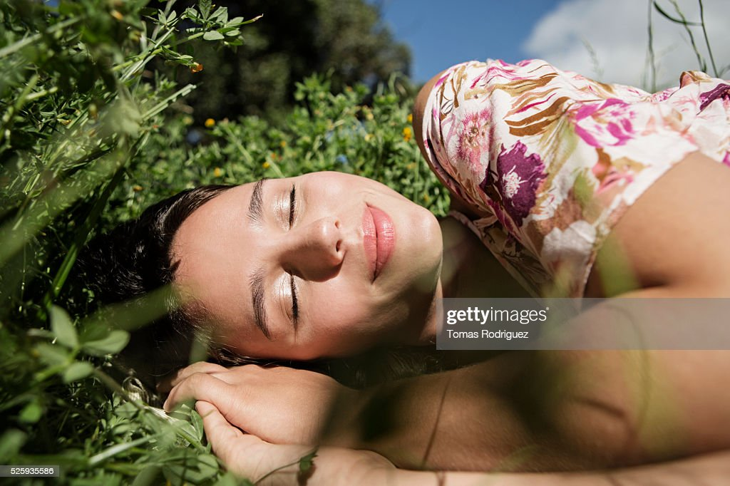 Portrait of young woman lying on grass with eyes closed : Stock-Foto