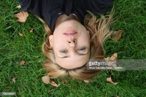 Portrait Of Young Woman Lying On Grassy Field