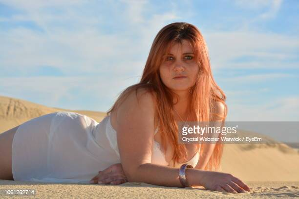 portrait of young woman lying on sand at desert - the webster stock pictures, royalty-free photos & images