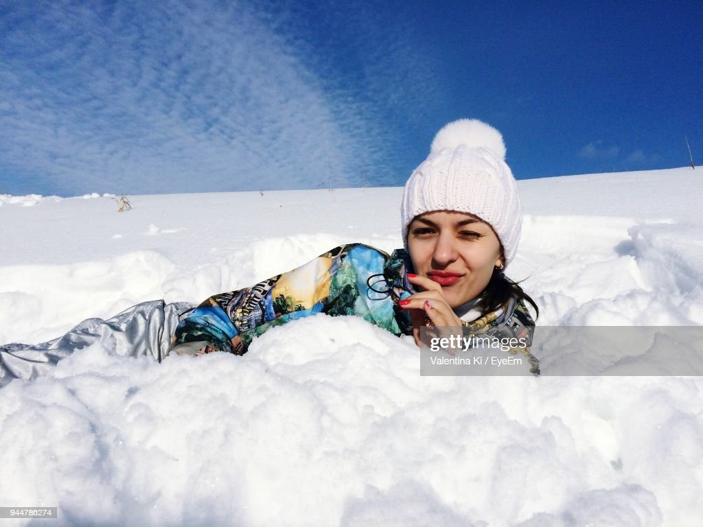 Portrait Of Young Woman Lying On Snow : Stock Photo