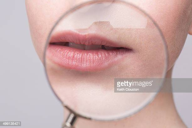 Portrait of young woman, magnifying glass on mouth