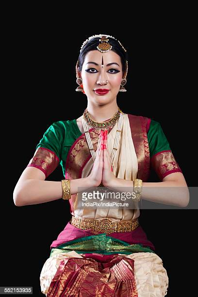 Portrait of young woman making Bharatanatyam gesture called Anjali on black background