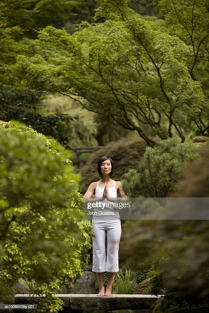 Portrait of young woman meditating on bridge in Japanese garden : Foto stock