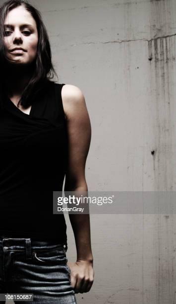 Portrait de jeune femme près du mur de ciment